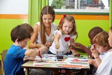 Kinder malen mit Erzieher im Kindergarten
